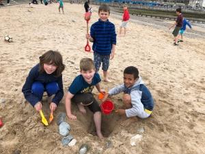 Boys digging in the sand in Llandudno