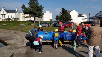 Boys carrying raft to water in Isle of Man